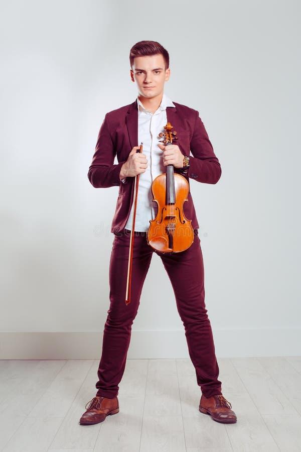 De viool en de strijkstok van de jonge mensenholding royalty-vrije stock foto's