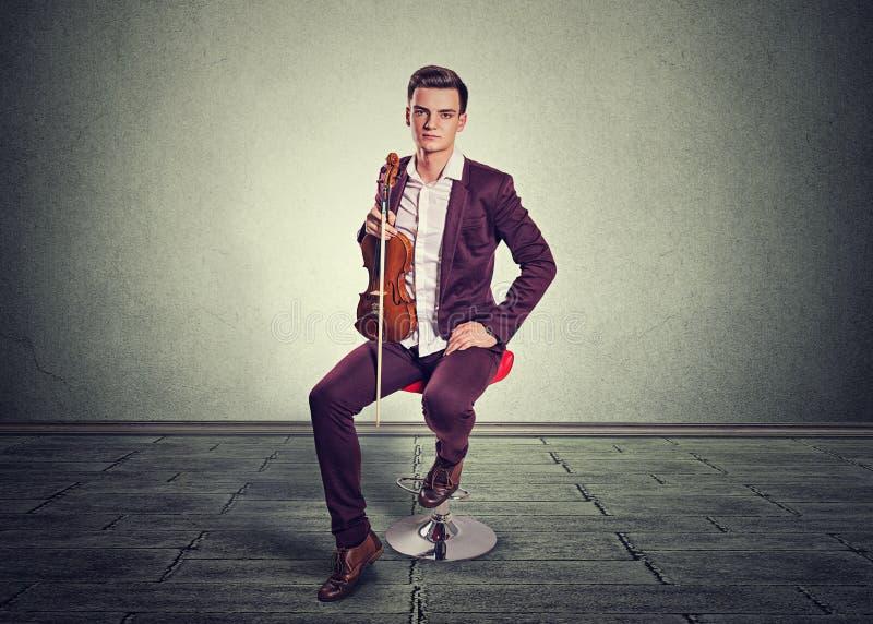 De viool en de strijkstok van de jonge mensenholding stock afbeeldingen