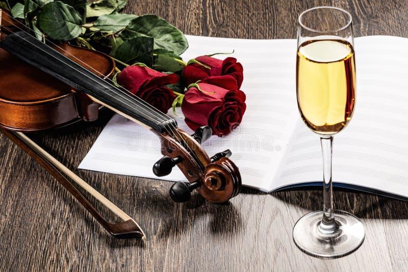 De viool, nam, glas champagne en muziekboeken toe stock foto's