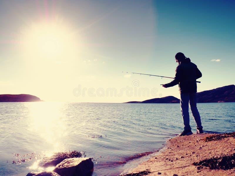 De vislijn van de visserscontrole en het duwende aas op de staaf, bereiden zich voor en werpen ver lokmiddel in vreedzaam water stock afbeelding