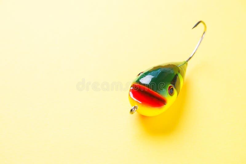 De vissende haken en de vissen gaven lokmiddelen op gele achtergrond met exemplaarruimte gestalte Selectieve nadruk stock foto's
