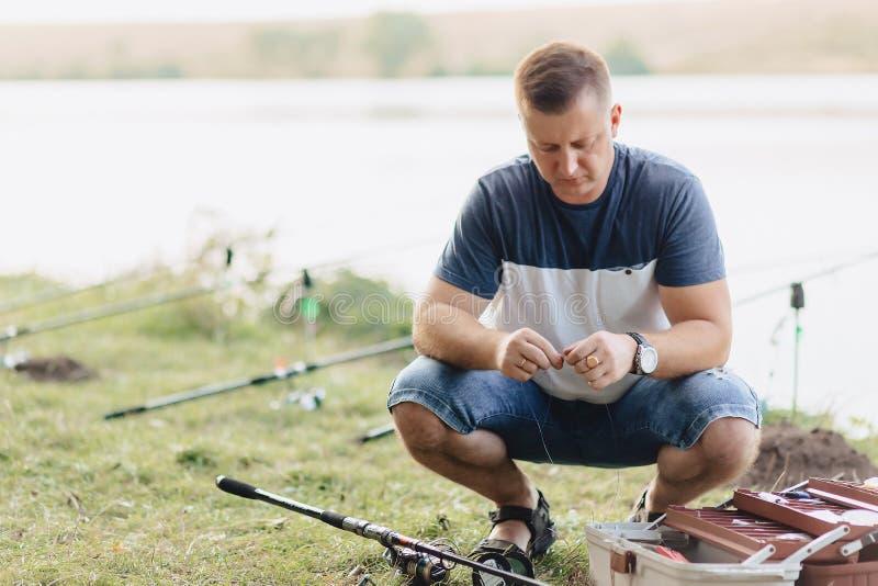 De visser bereidt breuk voor het vangen van karper bij meer in de zomer voor stock foto's