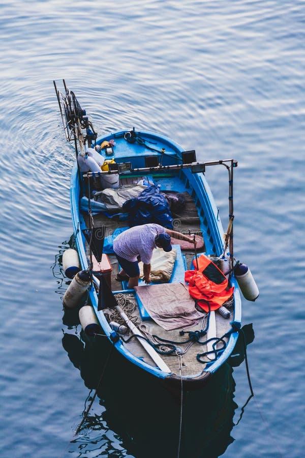 De visser bij dageraad bereidt de boot voor visserij voor stock fotografie