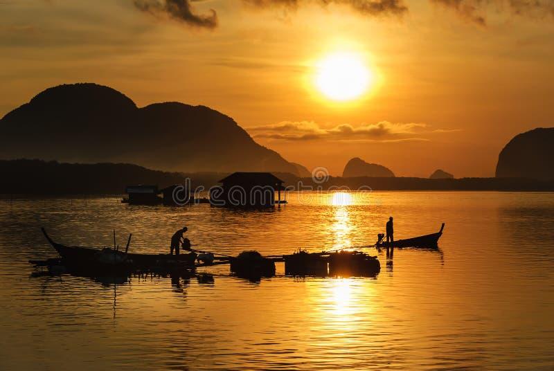 De Visser On Boat Fishing van de silhouetlevensstijl in Gouden Ochtend stock afbeeldingen