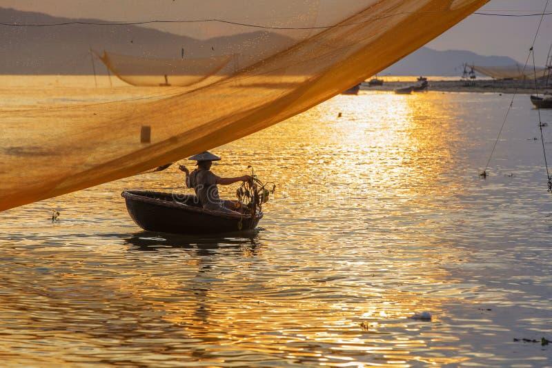 De visser controleert zijn netten in vroege ochtend op rivier in Hoian, Vietnam stock afbeeldingen
