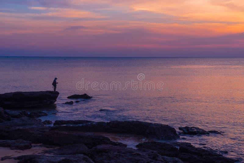 De visser die zich op de rots met zonsondergangachtergrond bevinden royalty-vrije stock foto