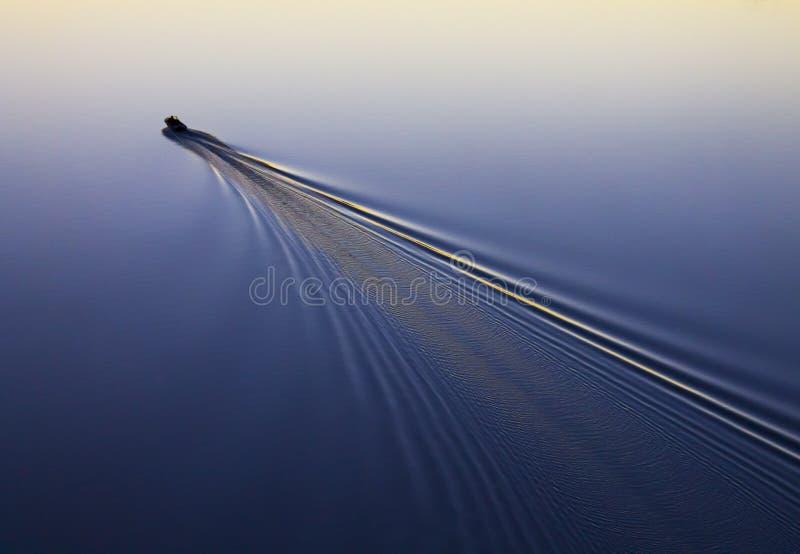 De visser drijft op een motorboot, rivier, meer, overzees, zonsondergang, zonsopgang stock foto's