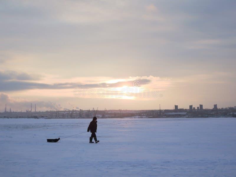 De visser gaat op een de wintervisreis met een ar in warme kleren en laarzen ruwe Zonnige ijzige dag royalty-vrije stock fotografie