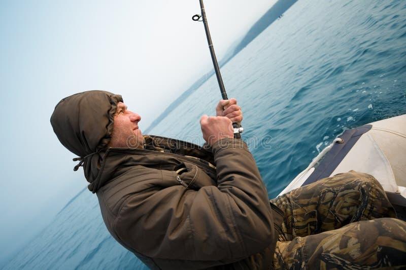 De visser houdt het met een sleeplijn vissen staaf royalty-vrije stock fotografie