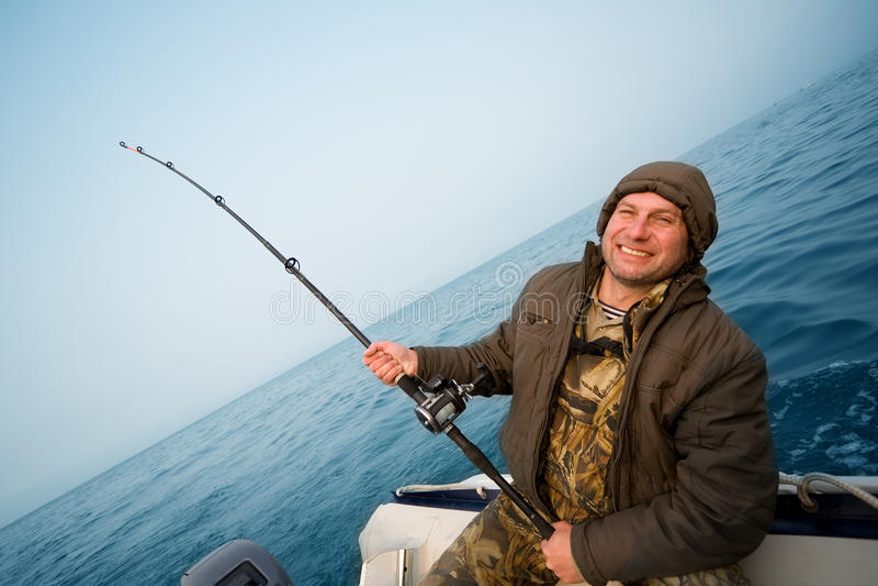De visser houdt het met een sleeplijn vissen staaf. stock afbeelding