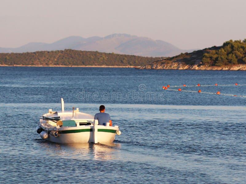 De visser op een boot zwemt uit om vissen in de stralen van de vroege zon te vangen Een mens op een boot vaart voorbij een steeng royalty-vrije stock foto