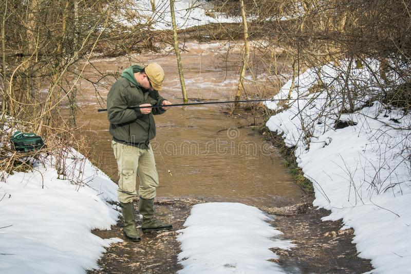 De visser probeert om vissen in de rivier te vangen stock afbeelding