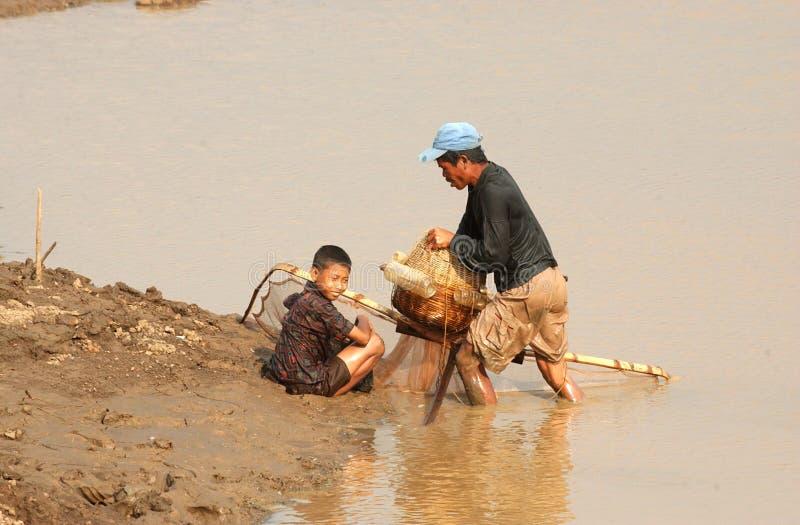 De visser streeft naar vissen in het dawuhan reservoir in Madiun stock fotografie