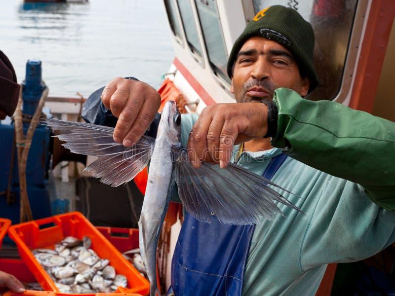 De visser toont een vliegende vis stock foto