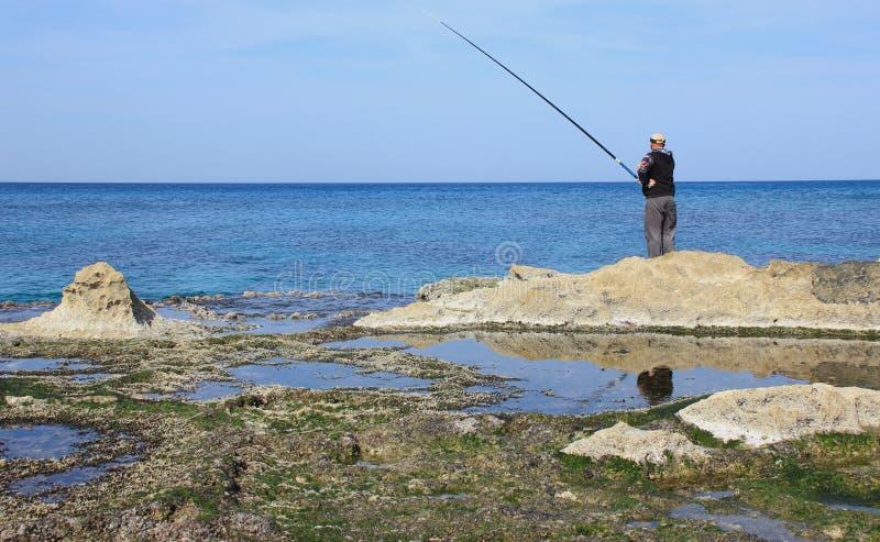 De visser vist op de kust van de Middellandse Zee stock afbeeldingen