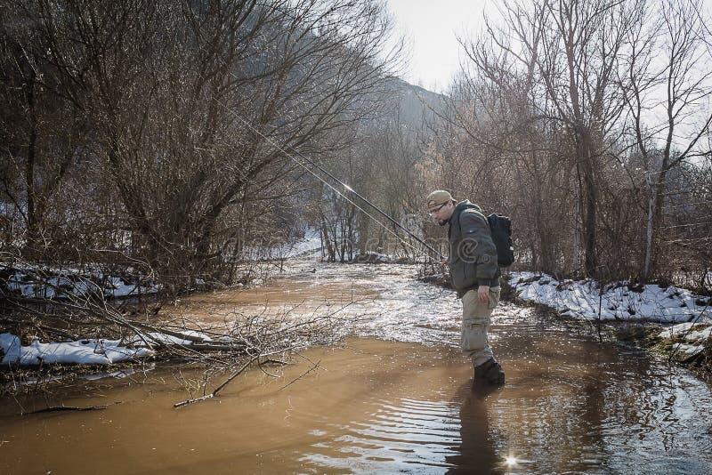 De visser waadt door het water en het streven van naar vissen royalty-vrije stock foto's