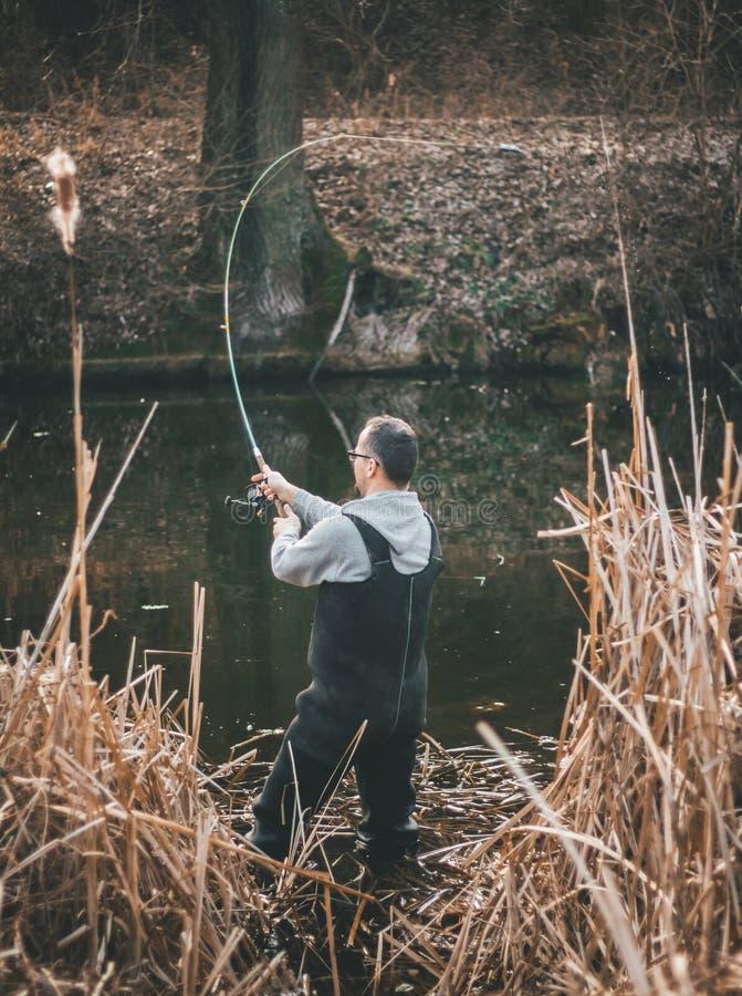 De visser werpt een haak Fisheman in het riet stock afbeelding