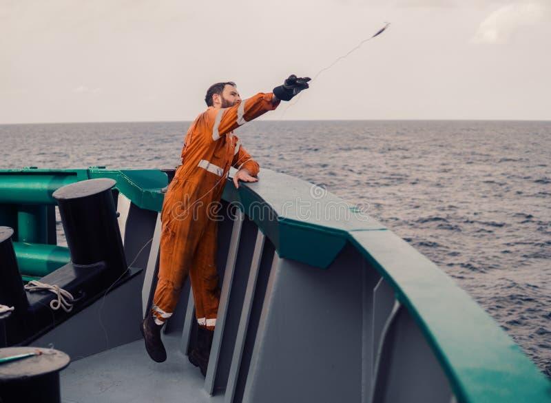 De visser werpt een haak op een schip voor het vangen van tonijnvissen Op zee visserij royalty-vrije stock fotografie
