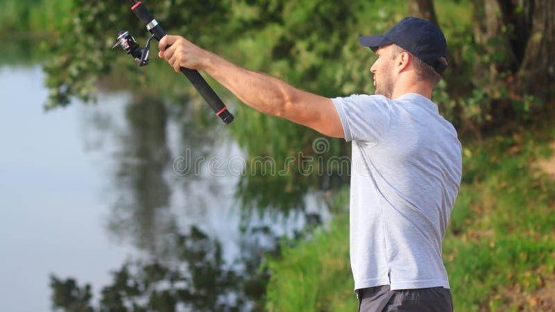 De visser werpt vislijn in rivier stock afbeelding