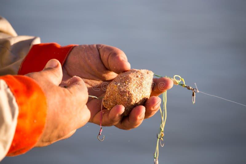 De visser zet aas op een hengelhaak stock foto