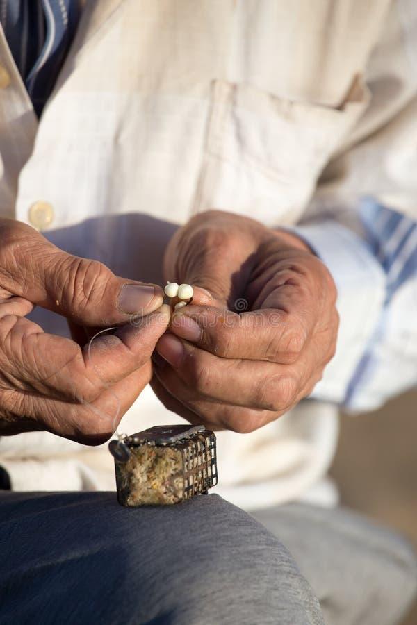 De visser zet aas op een hengelhaak stock afbeelding