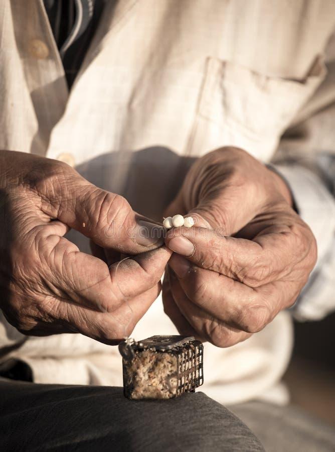 De visser zet aas op een hengelhaak royalty-vrije stock afbeeldingen