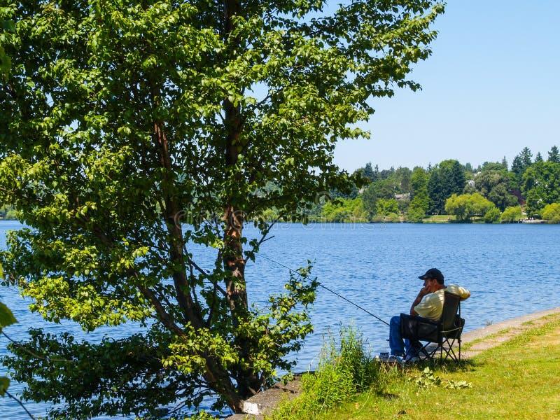 De visser zit alleen in schaduw van boom naast water geduldig wai royalty-vrije stock afbeelding