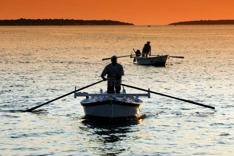 De visserij van de zonsondergang royalty-vrije stock afbeelding