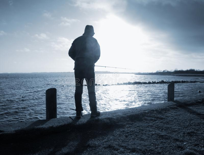 De visserij van mensensilhouet bij zonsondergang dichtbij het overzees stock fotografie