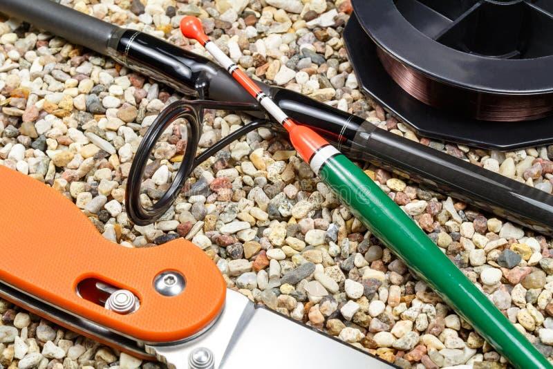 De visserij van vlotter met hengel, rol vislijn en mes op de steenachtige grond stock afbeelding