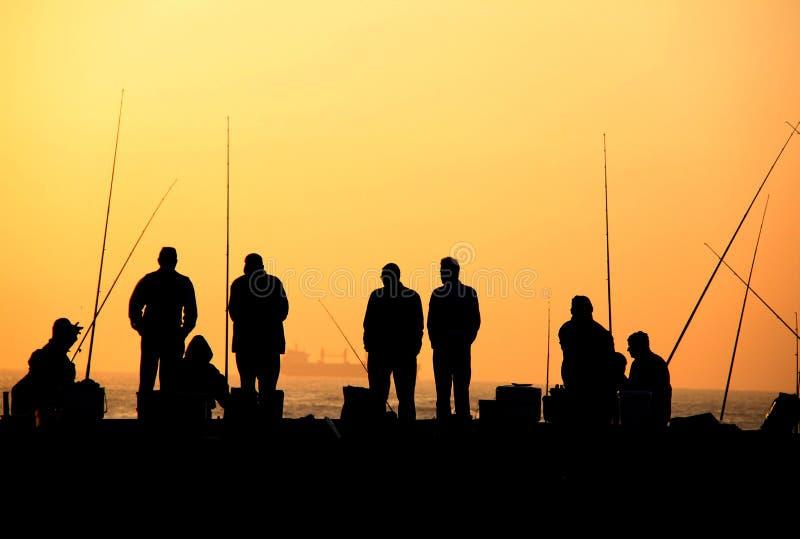 De vissers bij zonsopgang silhouetteren royalty-vrije stock afbeeldingen