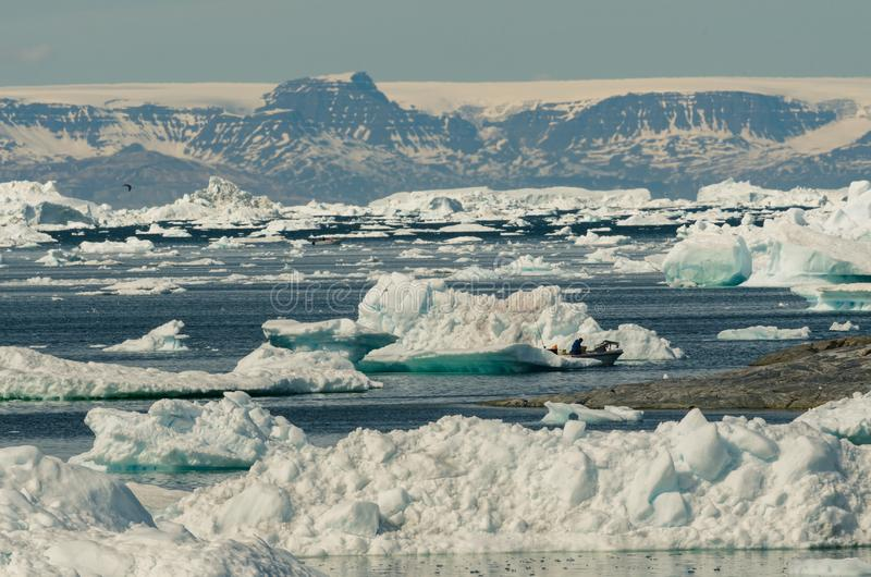 De vissers controleren hun vlekken onder de ijsbergen in Disko-Baai, Ilulissat, Groenland stock fotografie