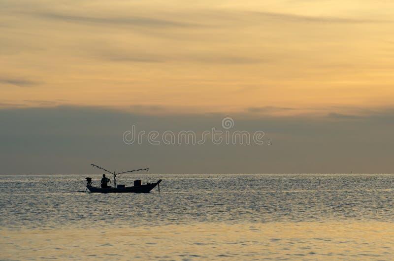 De vissers die op een boot vissen silhouetteren in het licht van de ochtendzonsopgang stock afbeeldingen
