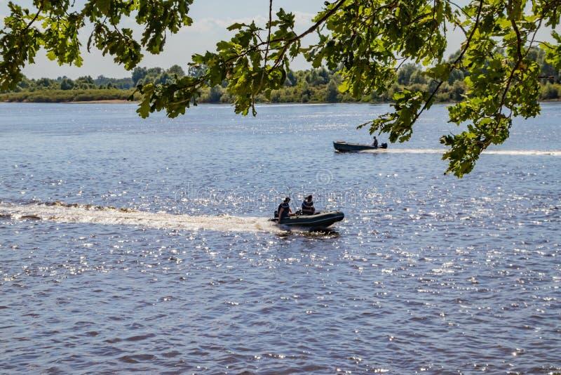 De vissers gaan motorboot op een rivier zoekend vissen op een zonnige de zomerdag stock afbeeldingen