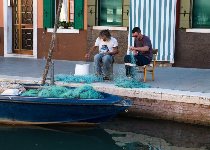 De vissers herstellen hun netten na een nacht van visserij stock foto