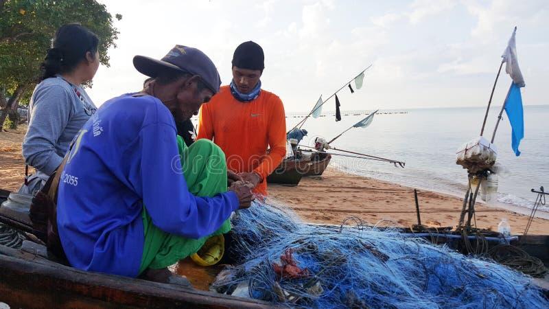 De vissers houden een net op de boot bij Jomtien-strand Pattaya, Thailand royalty-vrije stock foto