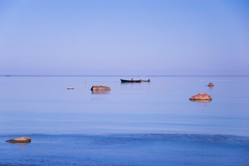 De vissers op de boten zetten netten en vallen op de vissen in het blauwe overzees onder de stenen stock afbeelding