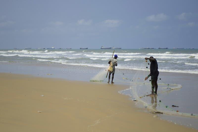 De vissers vangen vissen met netten dichtbij de kosten van Afrika Grote vrachtschepen en olietankers in Lagos, Nigeria, Afrika royalty-vrije stock foto