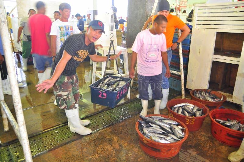 De vissers wegen tonijn bij de zeevruchtenmarkt stock fotografie