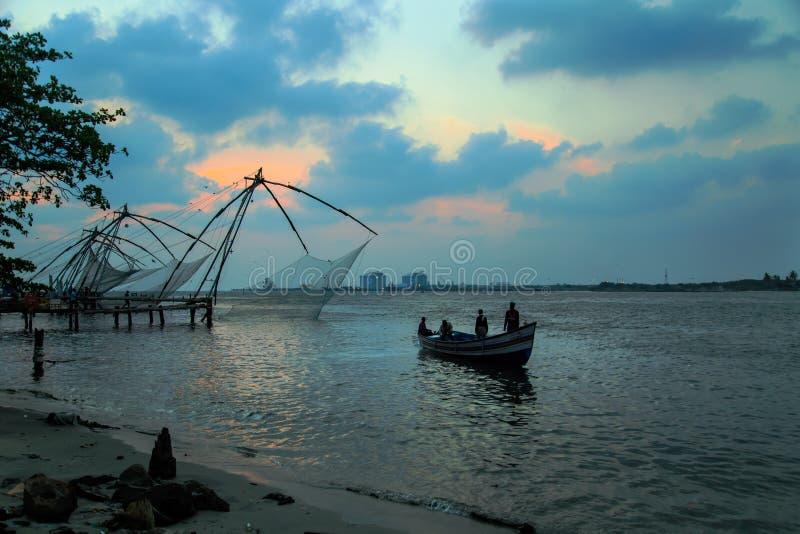 De vissers werpen Chinese netten in Fort Kochi stock afbeeldingen