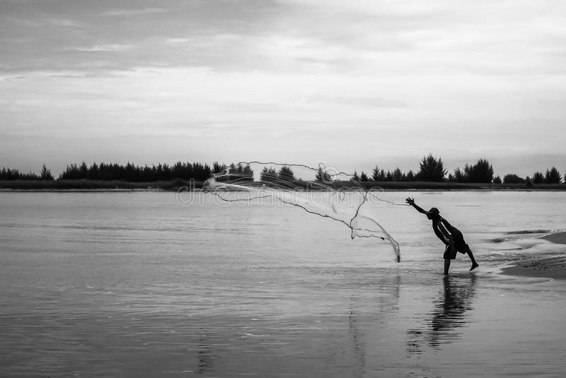De vissers werpen een visnet aan vangstvissen stock foto's