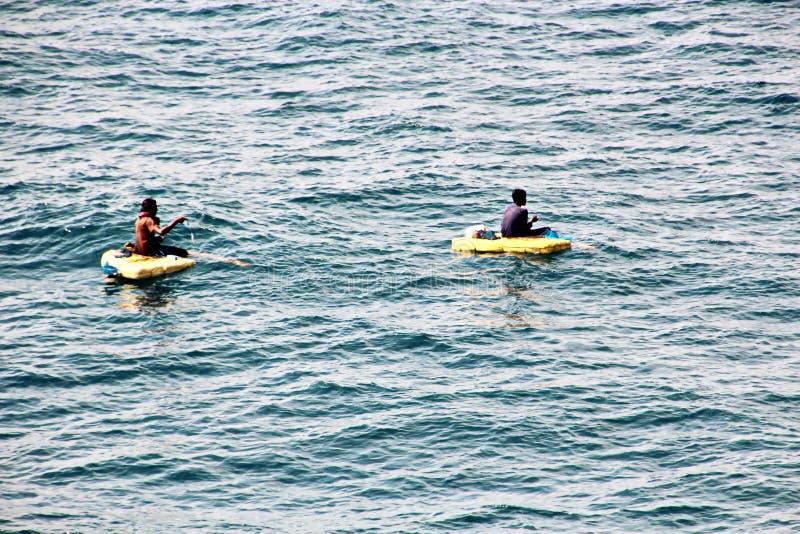 De vissers zijn bezig geweest met visserij op geïmproviseerde drijvende vlotten in de haven van Tuticorin, India stock foto's