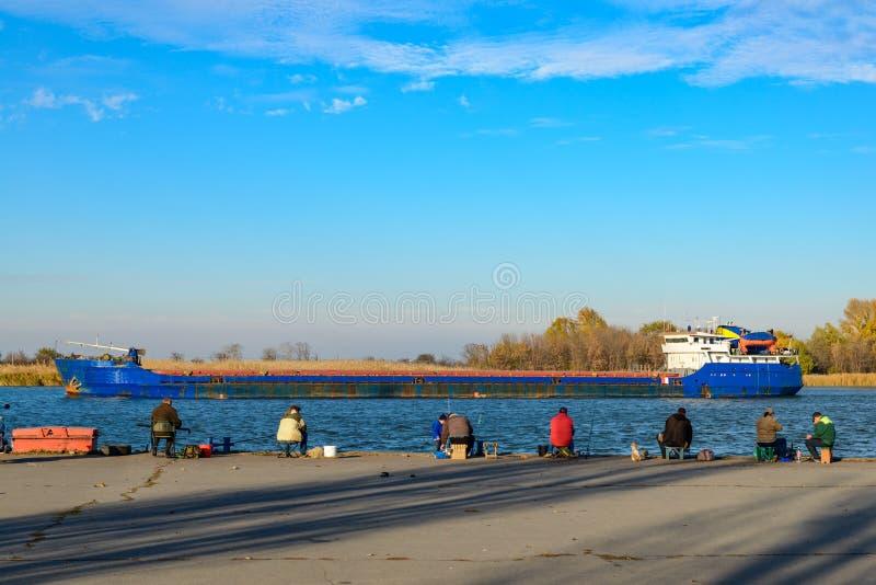 De vissers zitten op de pijler dichtbij de rivier en de vissen royalty-vrije stock foto