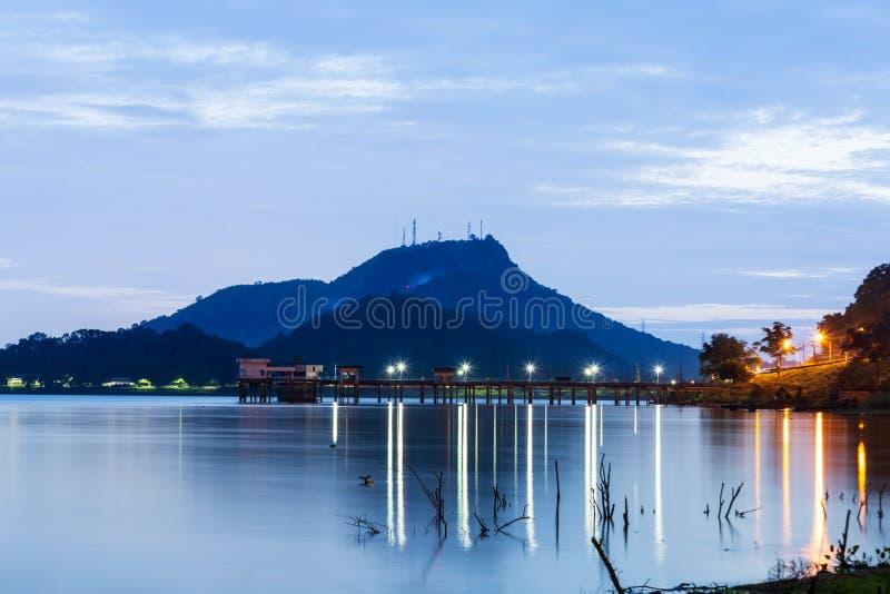 De vissersboot en het dode hout op de grote vijver riepen Bangpra-reservoir met grote berg als achtergrond in Chonburi Thailand,  royalty-vrije stock fotografie