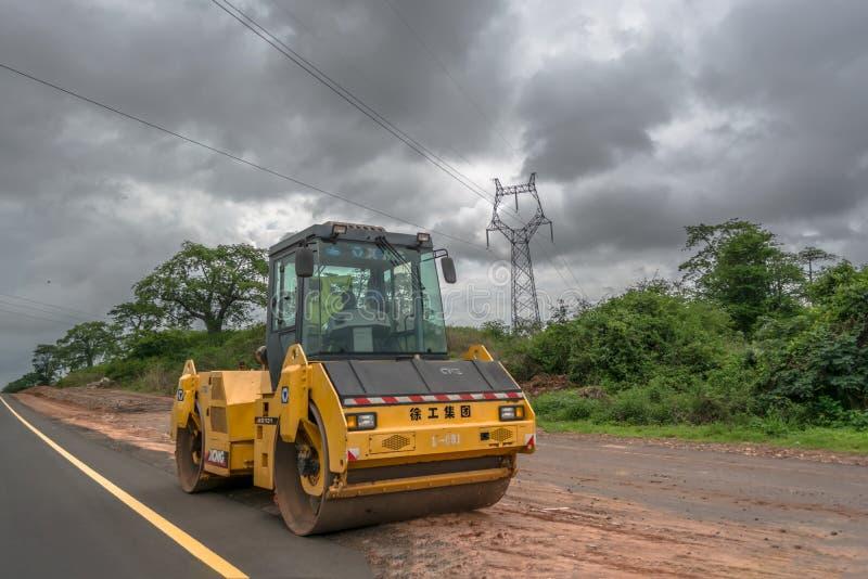 De vista completa de uma máquina do rolo de estrada, nivelando a terra com pessoa para conduzir imagens de stock