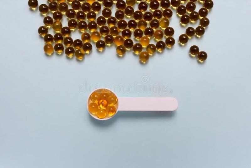 De vistraan, olie omega 3 van de Kabeljauwlever gelatineert capsules in metende lepel op blauwe achtergrond royalty-vrije stock foto's