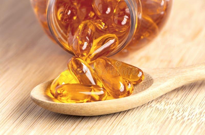 De vistraancapsules als dieetsupplement omega-3 bevatten en vitamine A die is hoog voor gezondheidszorg Zalmolie in lepel op royalty-vrije stock afbeelding