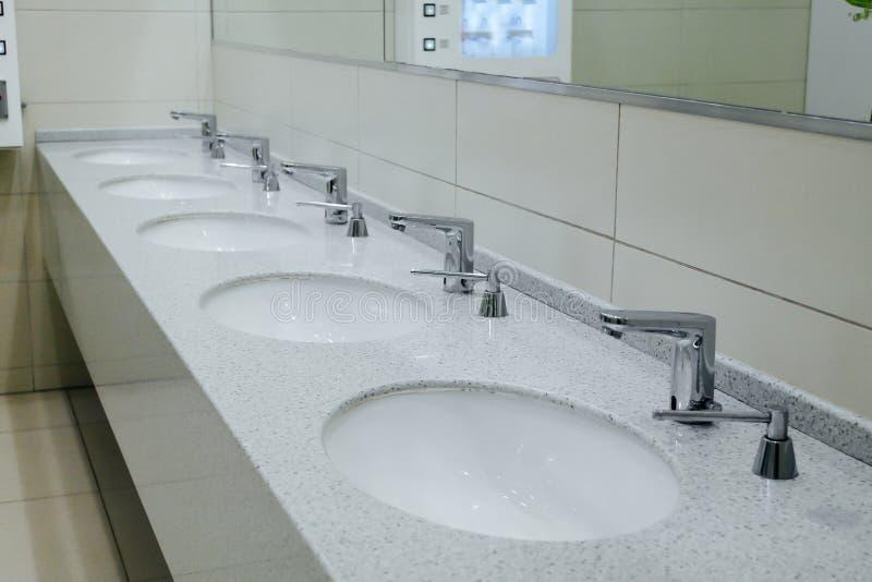 De vita badrumvaskarna och f?nstret royaltyfri foto