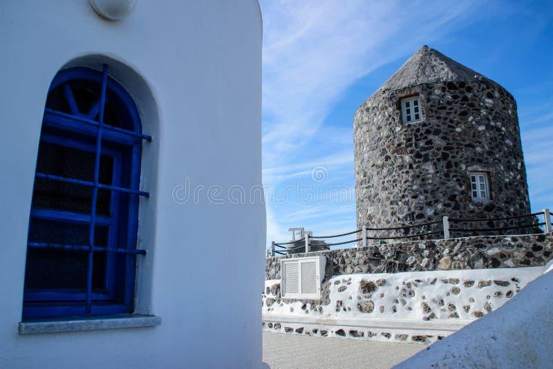 De vita husen av staden av Fira med blåa slutare och en väderkvarn fotografering för bildbyråer