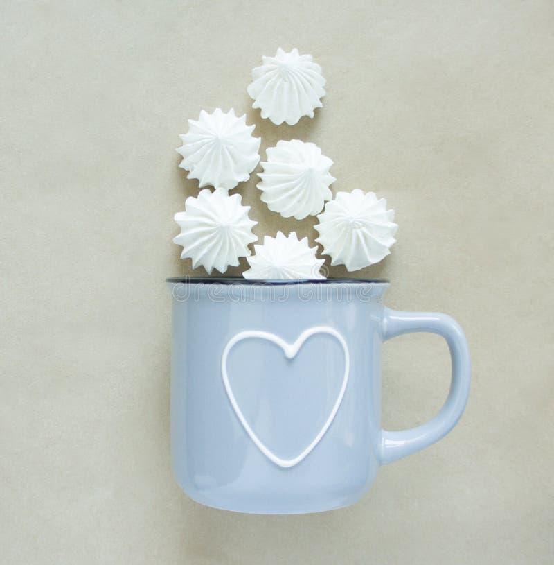 De vita merenguesna i en kopp på beige bakgrund, lägger framlänges, den bästa sikten En blå kopp med hjärta arkivbilder